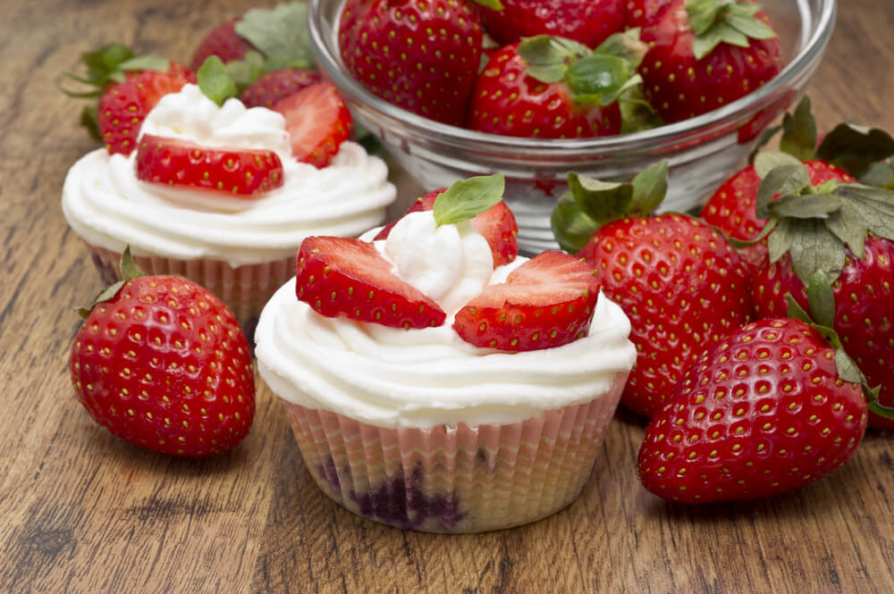 Chocolate muffins with strawberries and white cream on wooden table